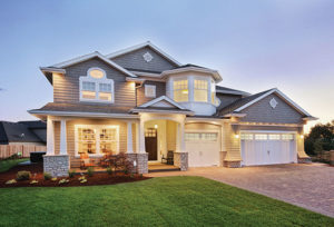Beautiful grey house with stone columns and green lawn lit up at dusk